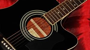 1381376_black_guitar_on_red_satin